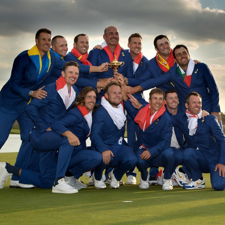 eam+Europe+posing+with+the+trophy+after+their+dominant+win+over+the+US%2C+with+their+country%E2%80%99s+flags+over+their+shoulders.