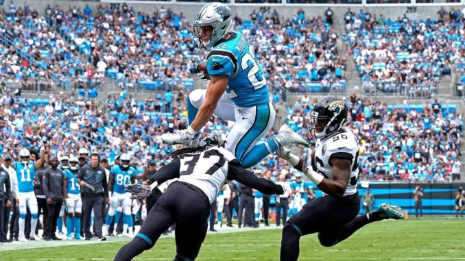 Panthers+RB+Christian+McCaffrey+leaps+over+defenders+for+a+Touchdown.+Many+consider+him+to+be+a+front+runner+for+the+MVP+Award.