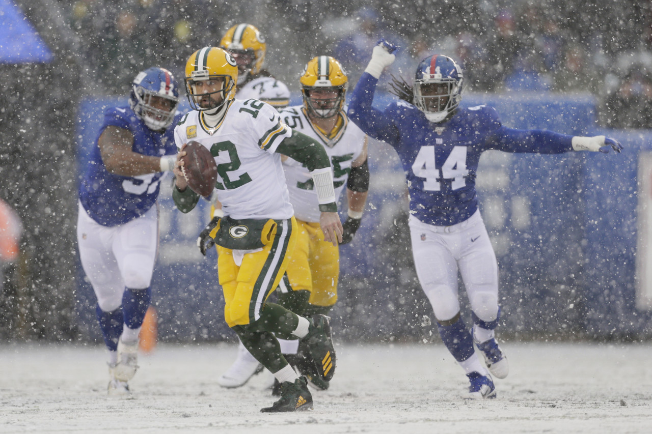 Packers QB Aaron Rodgers scrambles in the middle of a snowy game vs the Giants. The Packers would win the game 31-13.