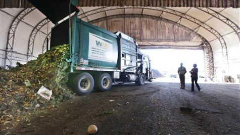In this Tuesday, Sept. 20, 2011 photo, visitors watch as a truck dumps compost materials inside a receiving area at the Cedar Grove processing facility in Everett, Wash. The city of Seattle began requiring residents in 2009 to recycle their food scraps along with weekly yard waste pickup and the results have been impressive: in 2010, the city's contractor kept 90,000 tons of Seattleites' banana peels, chicken bones and weeds out of landfills and converted that waste into rich compost prized in gardens. But the company processing that green waste has come under fire by citizens and others who complain of a pungent stench emanating from its two facilities located outside of Seattle. (AP Photo/Elaine Thompson)